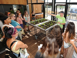 Photograph of man pointing to a planter table with a small crowd of people looking on. The man is a team member from the University at Buffalo Solar Decathlon 2015 team, and he is giving a tour of the team's GRoWlarium, which is a combination solarium and green house