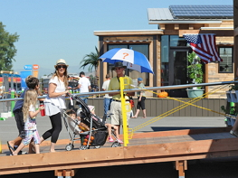 Photograph of a woman pushing a stroller with small children, and more children walk behind her, up a ramp to a competition house at the U.S. Department of Energy Solar Decathlon 2015 in California. A man, a volunteer for Solar Decathlon, stands by ready to answer questions.