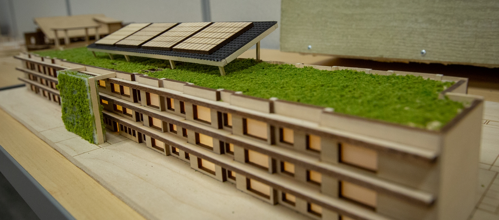 Photo of a wooden model from the 2019 Design Challenge. The model building appears to have solar panels on the roof as well as grassy areas.