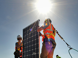 Photo of a woman and man, both wearing yellow hard hats and orange safety vests carrying a photovoltaic panel (solar electric panel) on the roof of a Solar Decathlon house. The sun is shining brightly in the sky behind them. They are both clipped into safety harnesses appropriate for working at heights.