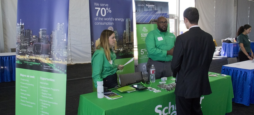 Photo of a man in a business suit speaking with two people at a sponsor booth.