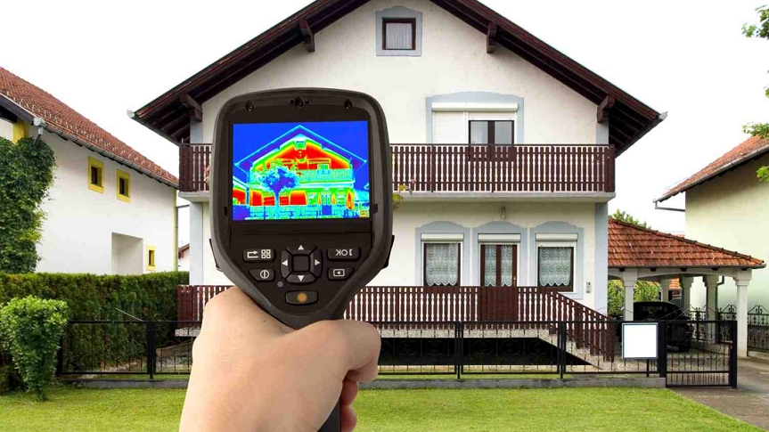 A photo of a person holding a thermal sensor up to a house.