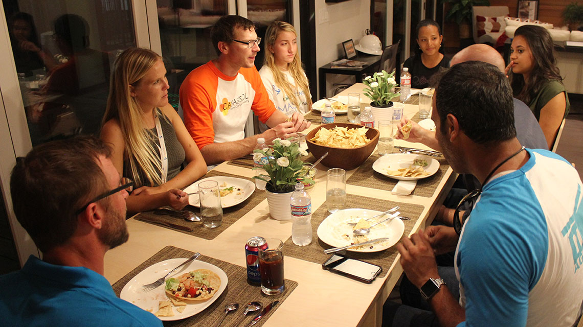 Photo of people sitting around a table eating and talking during a dinner party.