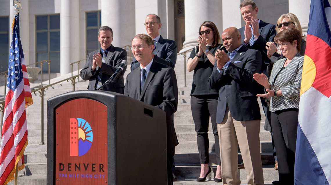 Photo of Dr. Franklin Orr speaking from behind a podium with a Denver logo. A group of people stands behind him.