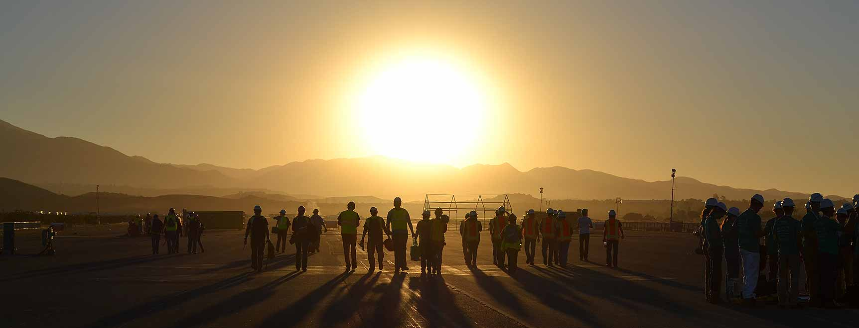 Photo of students in construction gear walking under a rising sun.