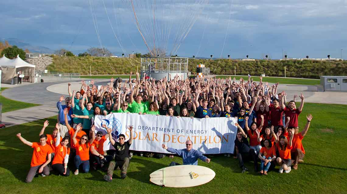 Photo of a large group of students cheering beneath a hot air balloon and holding a sign that says U.S. Department of Energy Solar Decathlon.