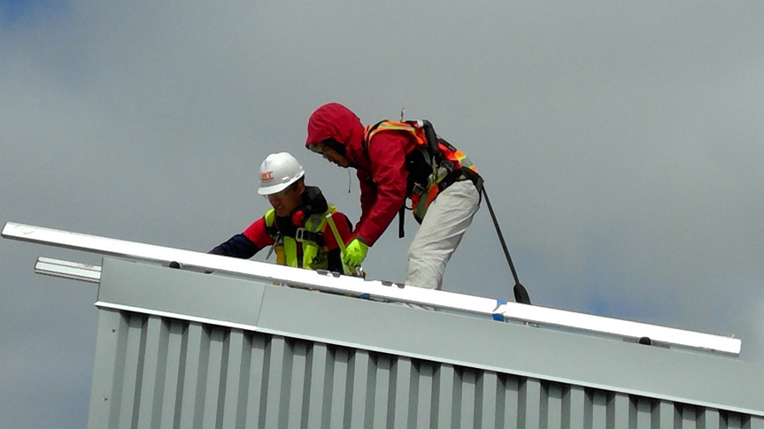 Photo of two people working on a roof of a building during the 2017 Solar Decathlon.