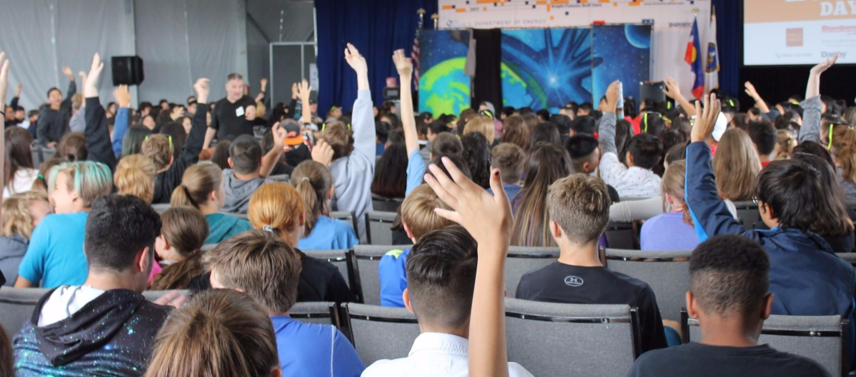 Photo of backs of middle school boys and girls sitting in chairs and raising their hands to answer questions during an education session inside a white tent at Solar Decathlon 2017. The students are facing a stage and a projection screen.