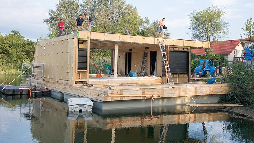 Photo of Team Austria reconstructed LISI in the middle of a lake after winning Solar Decathlon 2013.