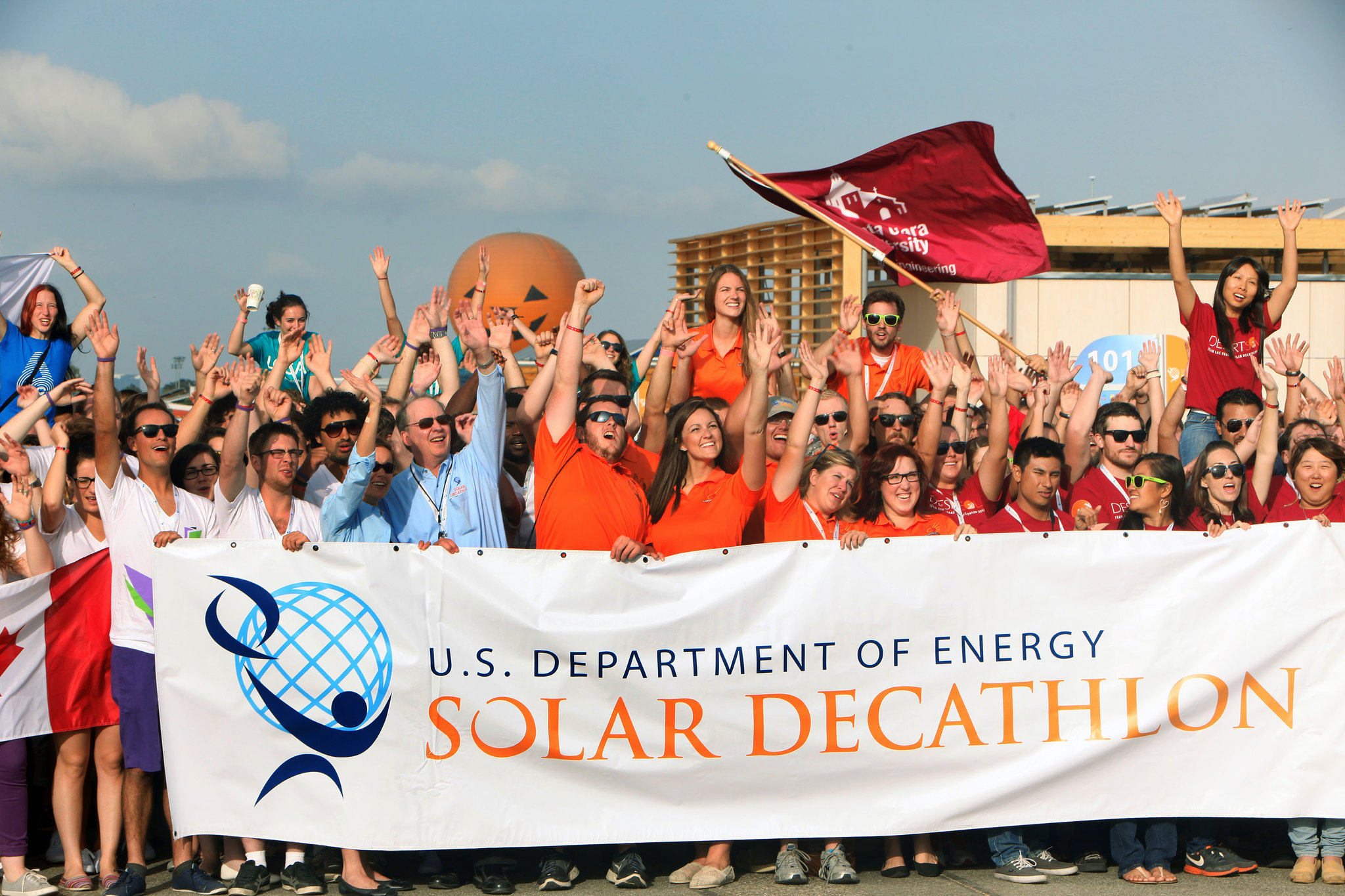 A group of people holding a solar decathlon banner.