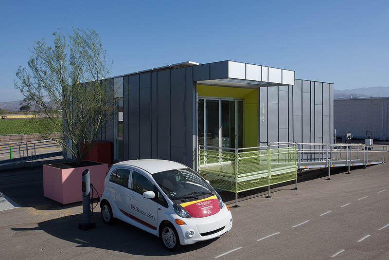 Photo of an electric vehicle parked next to a charging station beside a Solar Decathlon competition house.