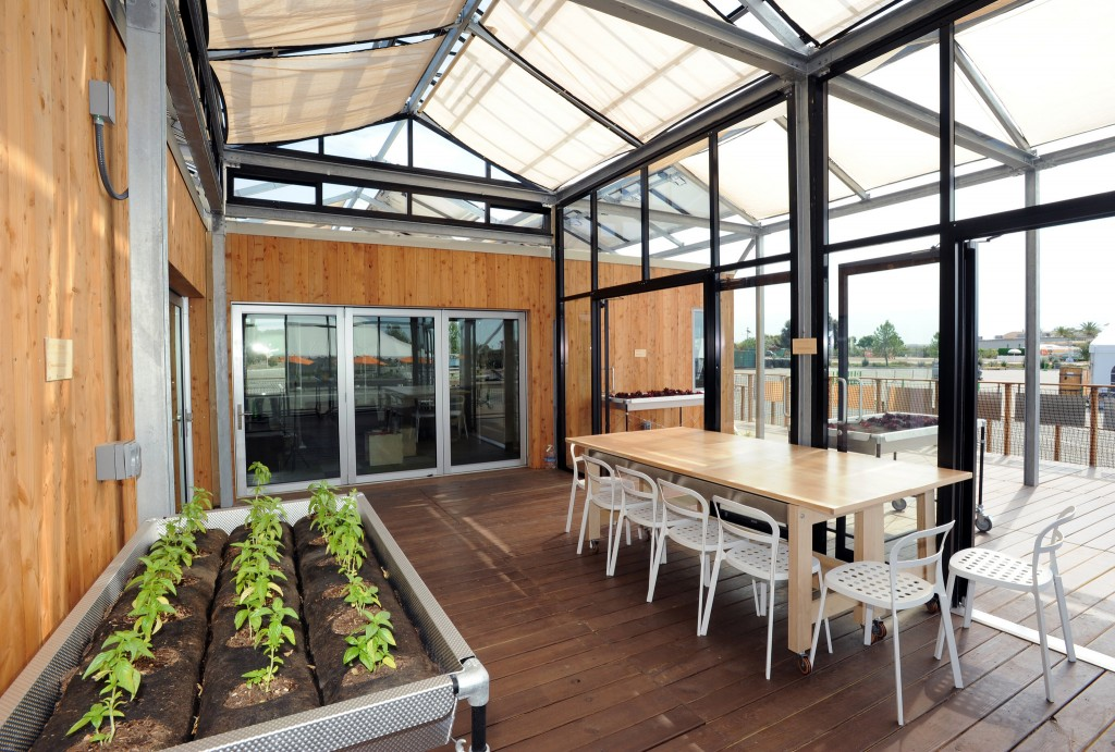 A canopy covering the enclosed portion of the University at Buffalo team's GRoW Home serves as a trellis for plants, shades the house and deck to reduce cooling loads, and provides outdoor living space. Photo from Thomas Kelsey/U.S. Department of Energy Solar Decathlon