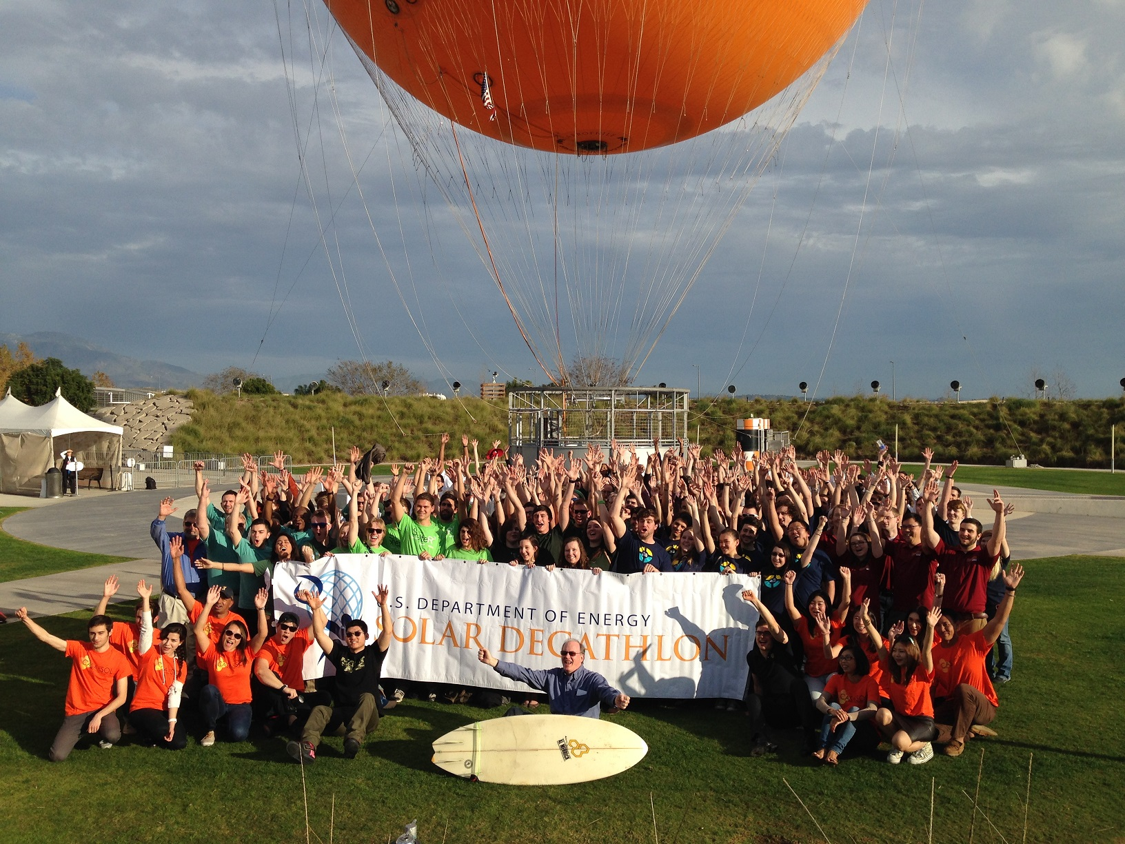 "Photo of a large group of cheering people in front of a balloon and holding a banner that reads, ""U.S. Department of Energy Solar Decathlon."""
