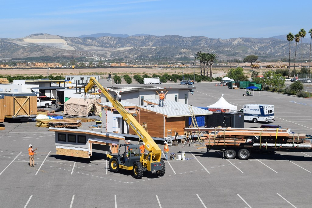 Aerial photo of the Solar Decathlon village during construction, showing a crane and several houses.