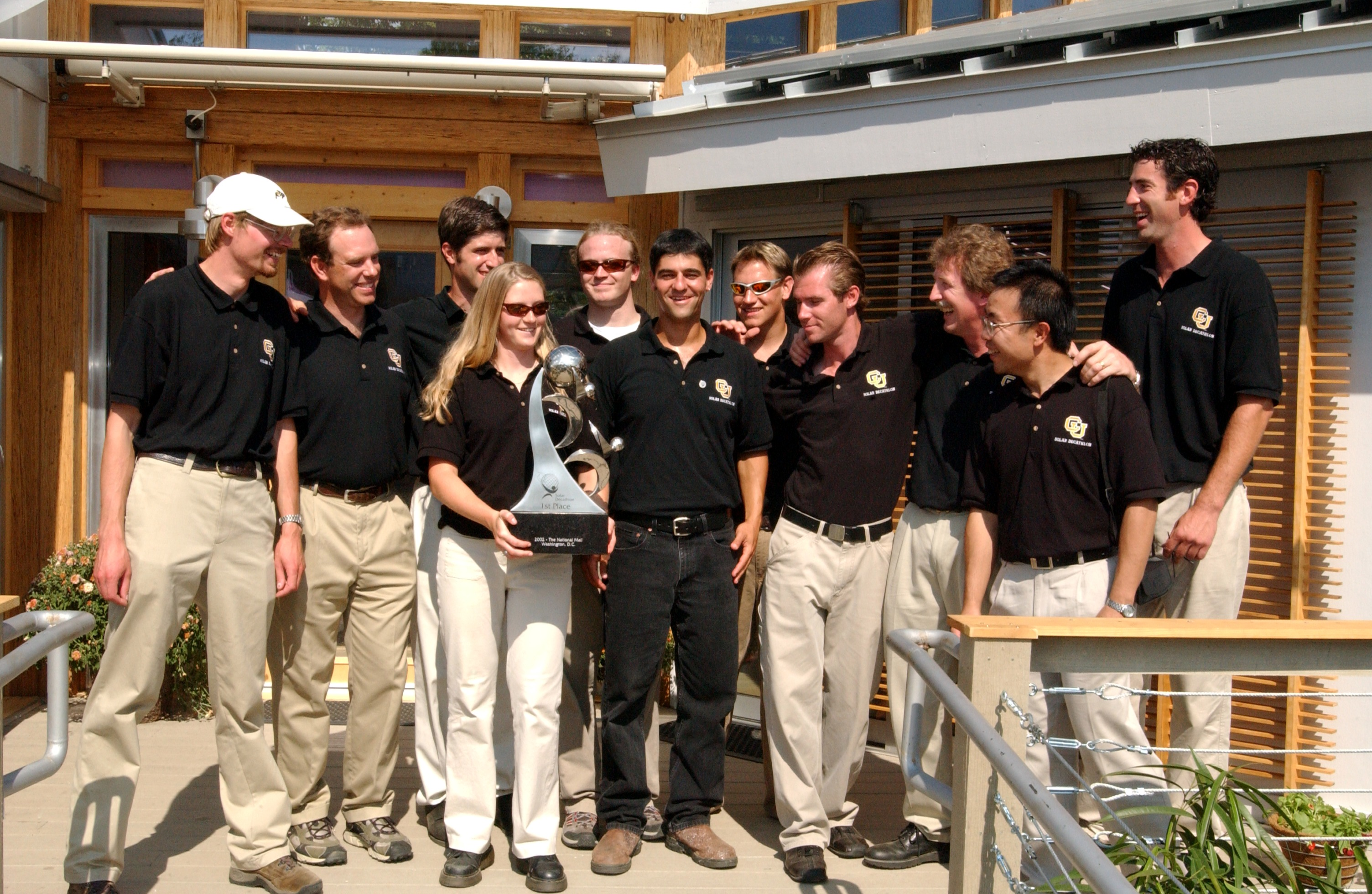 Photo of a group of men standing around a woman who is holding a large trophy.