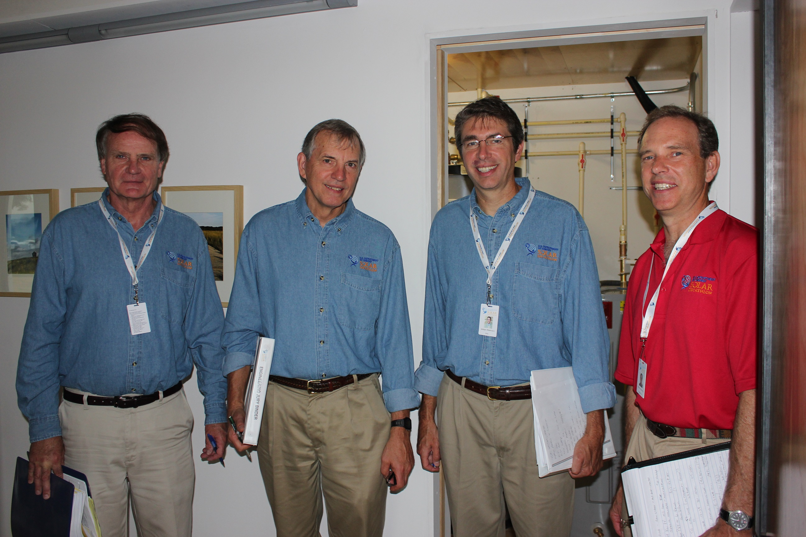 Photo of four men standing in a row and smiling at the camera.