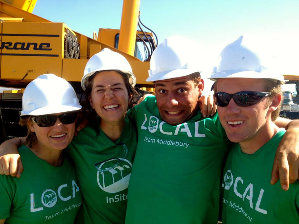 Photo of a group of smiling people wearing hard hats.