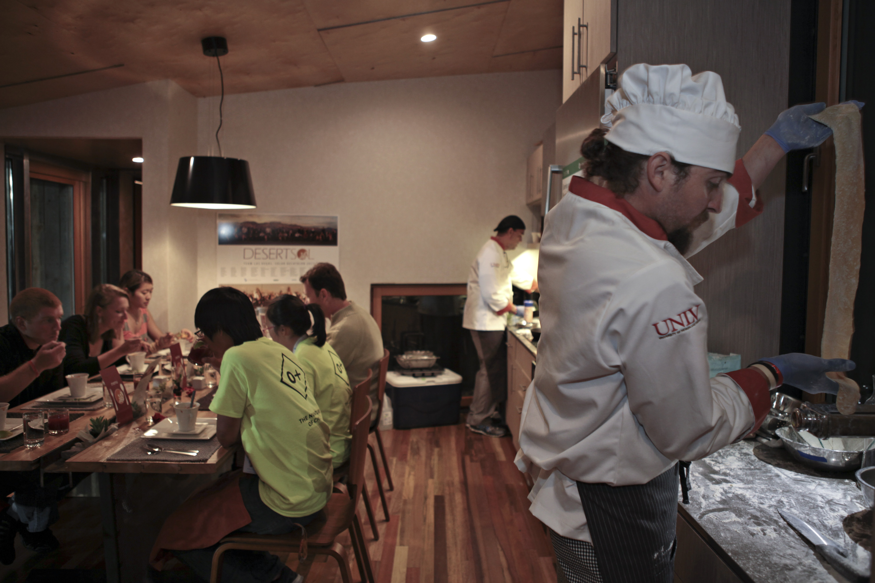 Photo of a man wearing a chef's hat cooking at a stove, with people sitting at a table in the background.