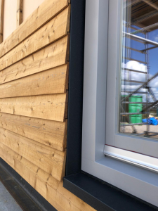 Picture of a home's exterior window with wooden framing panels partially installed.