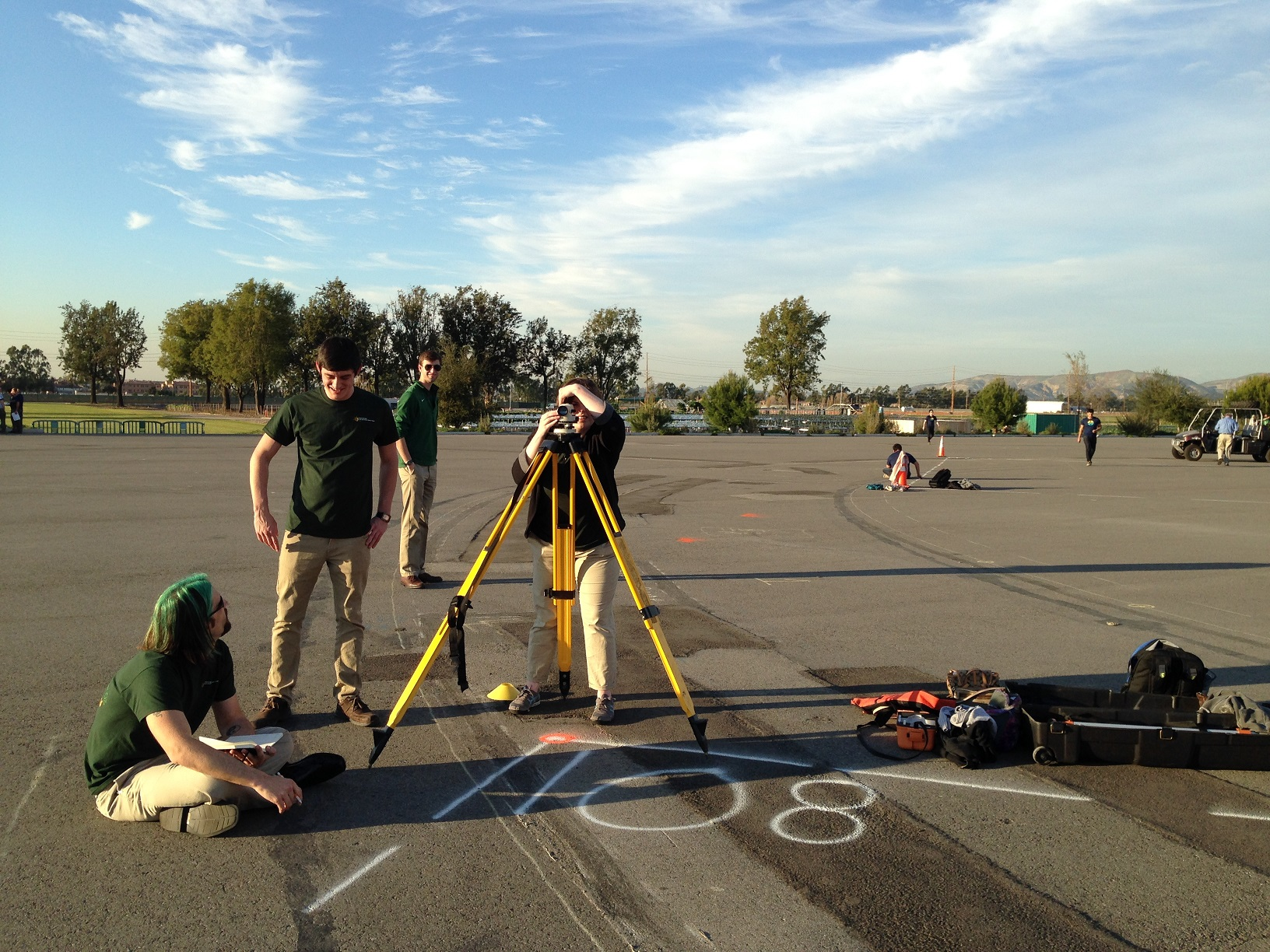 Photo of three people taking measurements with surveying equipment on a tripod.