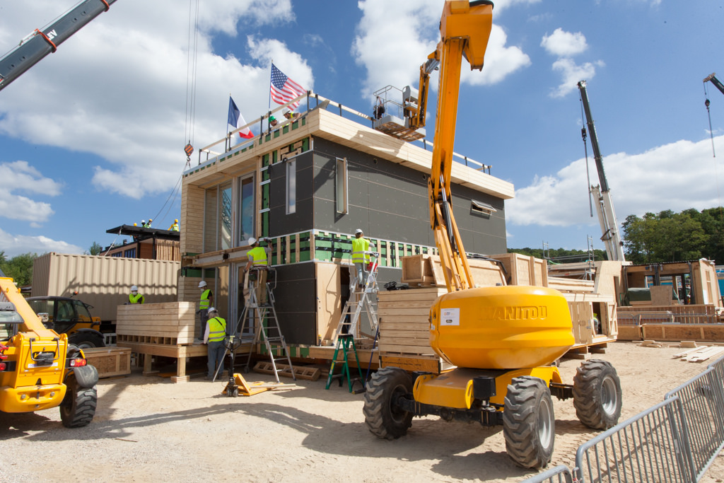 Photo of a partially constructed house with two stories and French and U.S. flags waving on the roof.