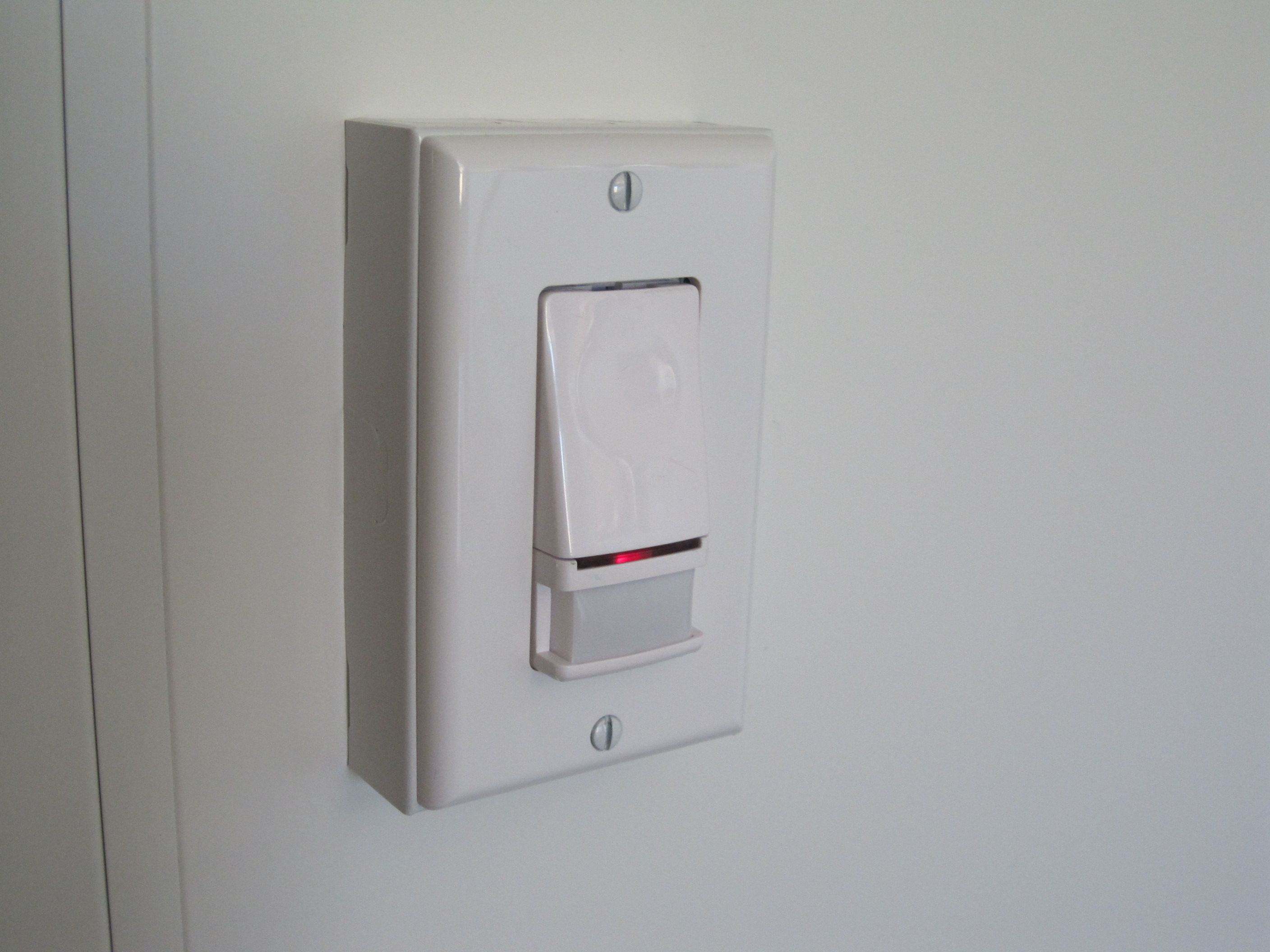 Photo of a vacancy sensor light switch on the wall.