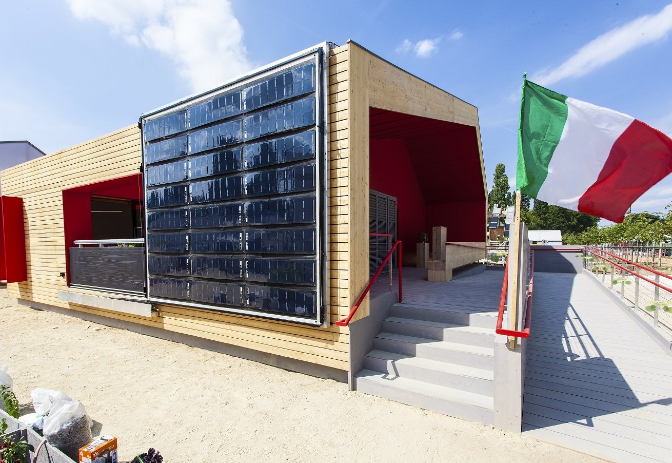 Photo of a modern house with solar PV panels on its side and an Italian flag near the front entrance.