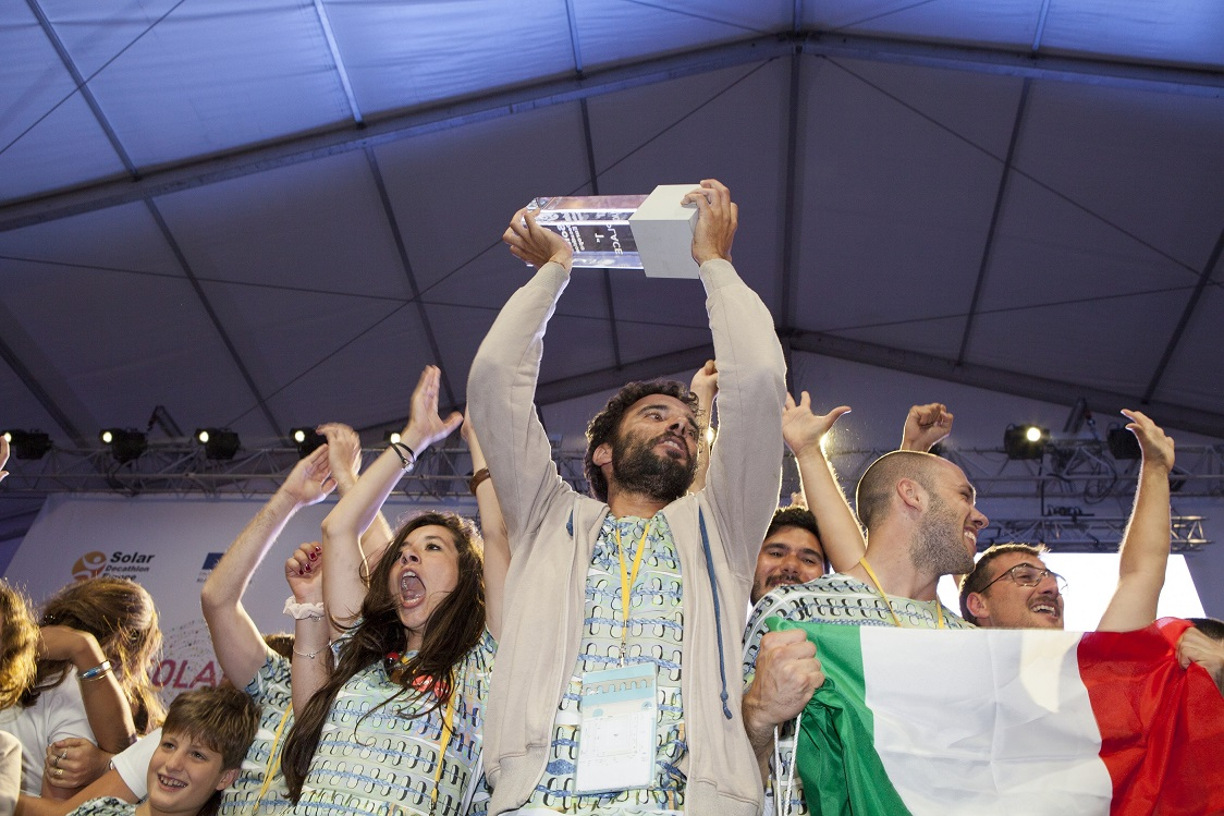 Photo of a group of cheering people holding an Italian flag and a first-place trophy.