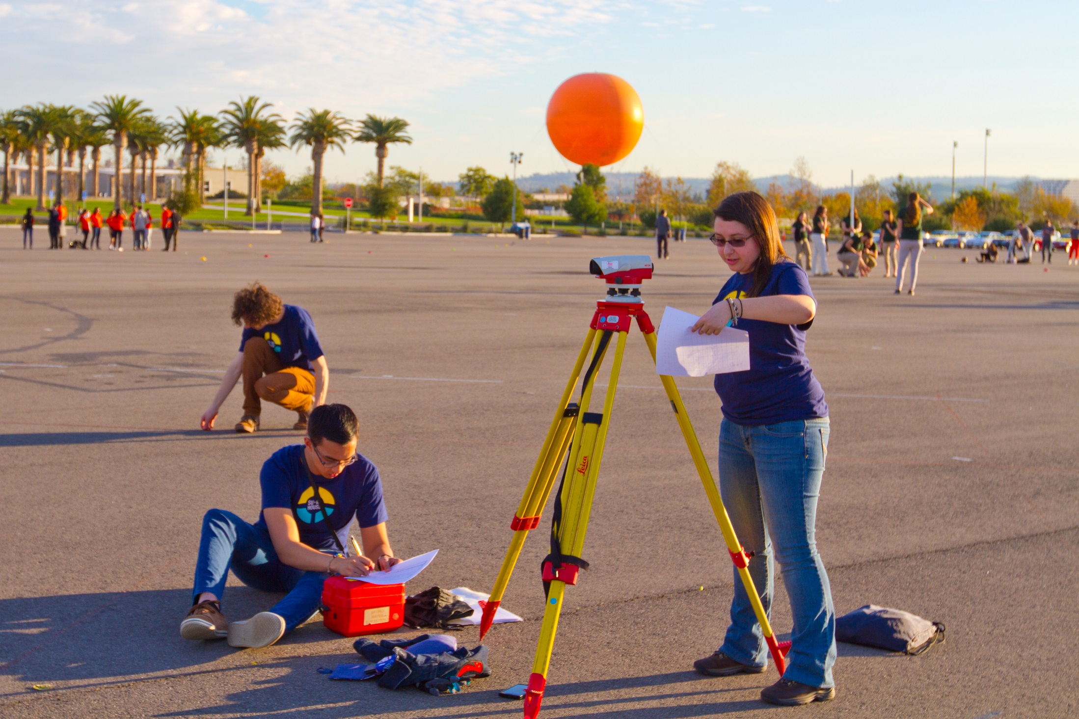 Photo of two people taking measurements with surveying equipment on a tripod.
