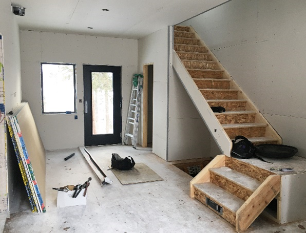Inside view of a a new construction home, with unfished walls and stairs.