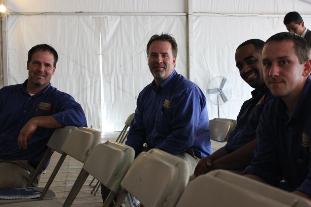 Photo of four men sitting in folding chairs inside a tent.
