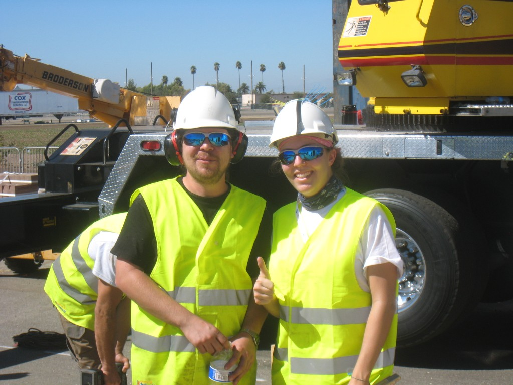 Photo of two decathletes wearing hard hats, safety glasses, and safety vests.