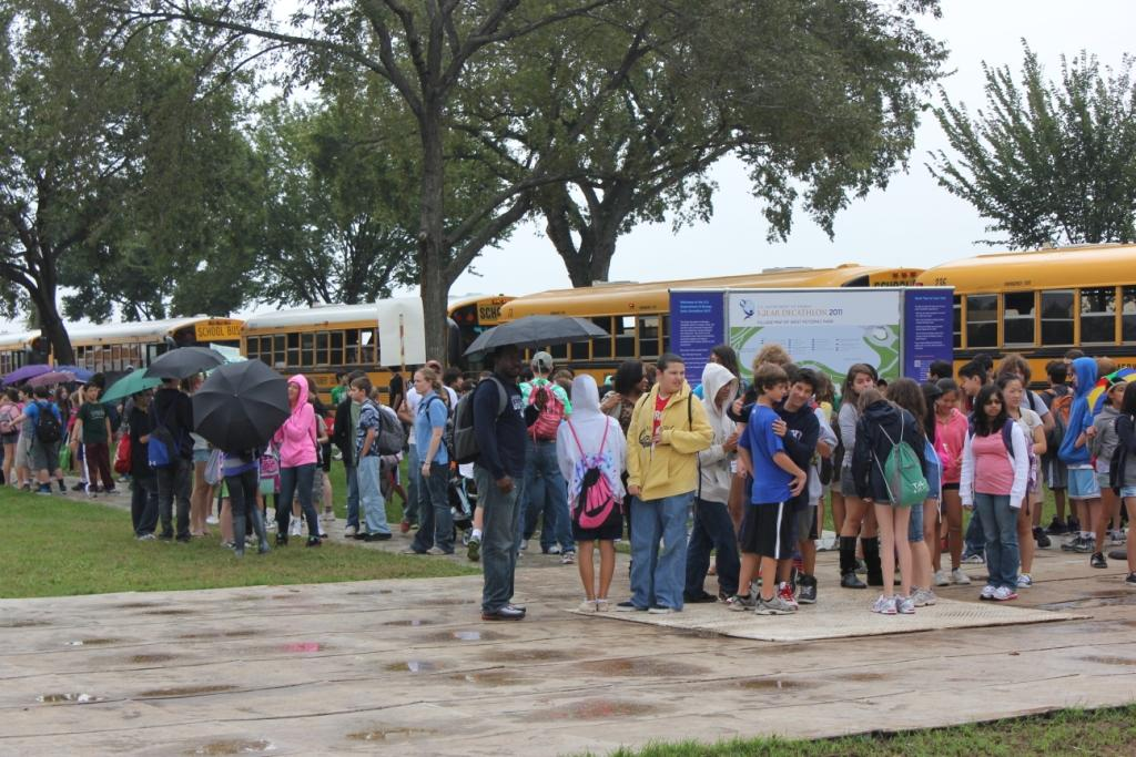 Photo of a large group of students lined up in front of buses.
