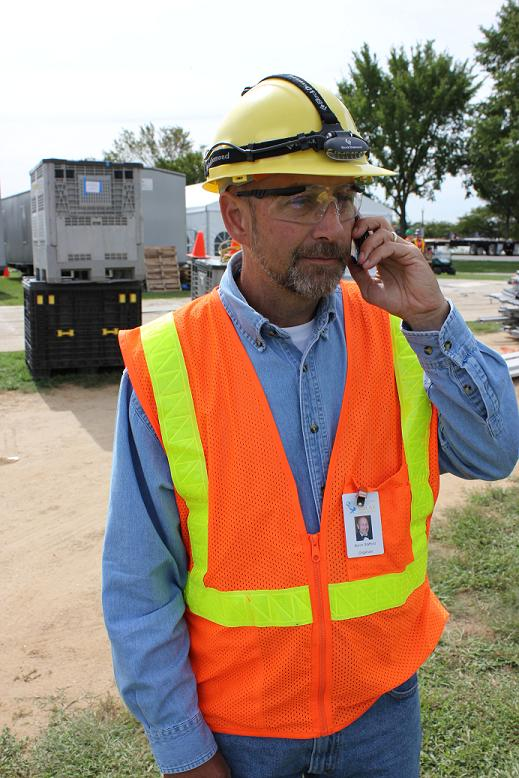Photo of a man wearing a hard hat, safety glasses, and safety vest and talking on a mobile phone.