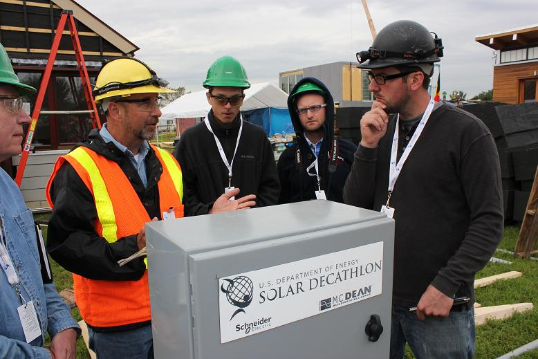 Photo of men in hard hats standing around an organizer utility panel.