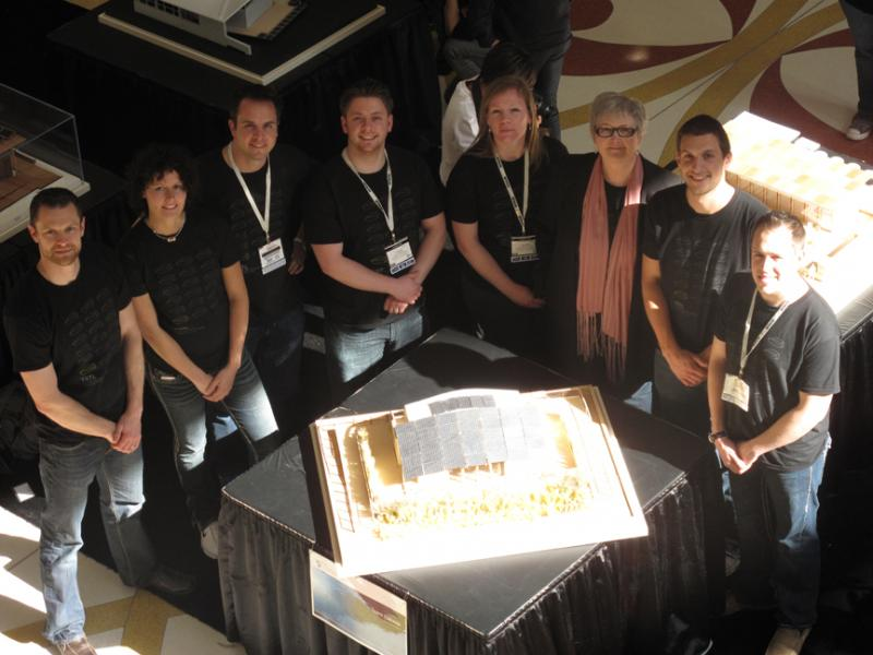 Photo of a group of people standing around a small table with a model of TRTL.