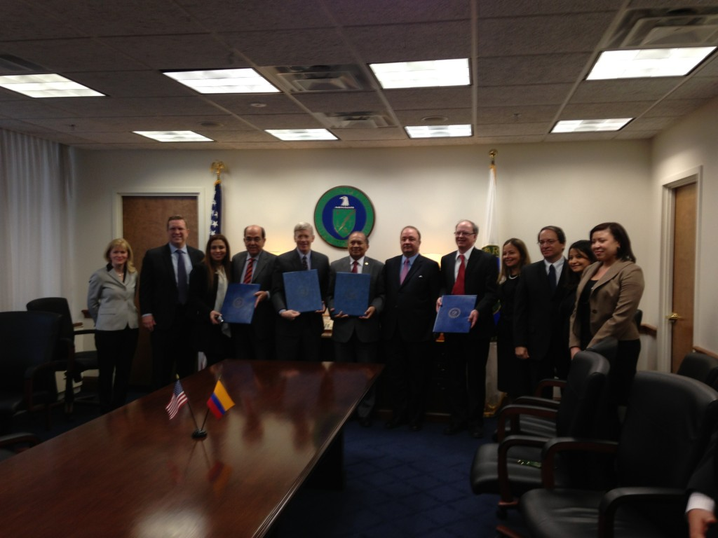 Photo of a group of people standing in meeting room around a table. They hold duplicate copies of an MOU. In the background is the U.S. Department of Energy seal. On the table are small American and Colombian flags.