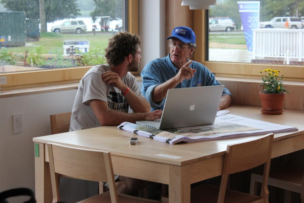 Photo of a student decathlete reviewing construction documents and online data with Matt Hansen.