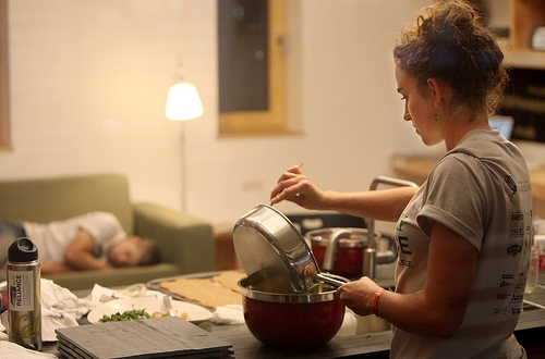 Photo of a woman cooking at a counter. In the background, a man sleeps on a couch.