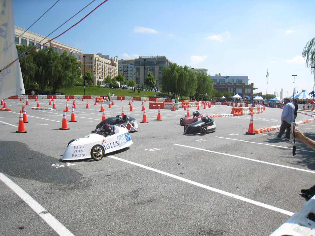 Photo of electrathon vehicles racing on course marked by traffic cones.