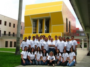Photo of a group of students posing in front of a yellow building.