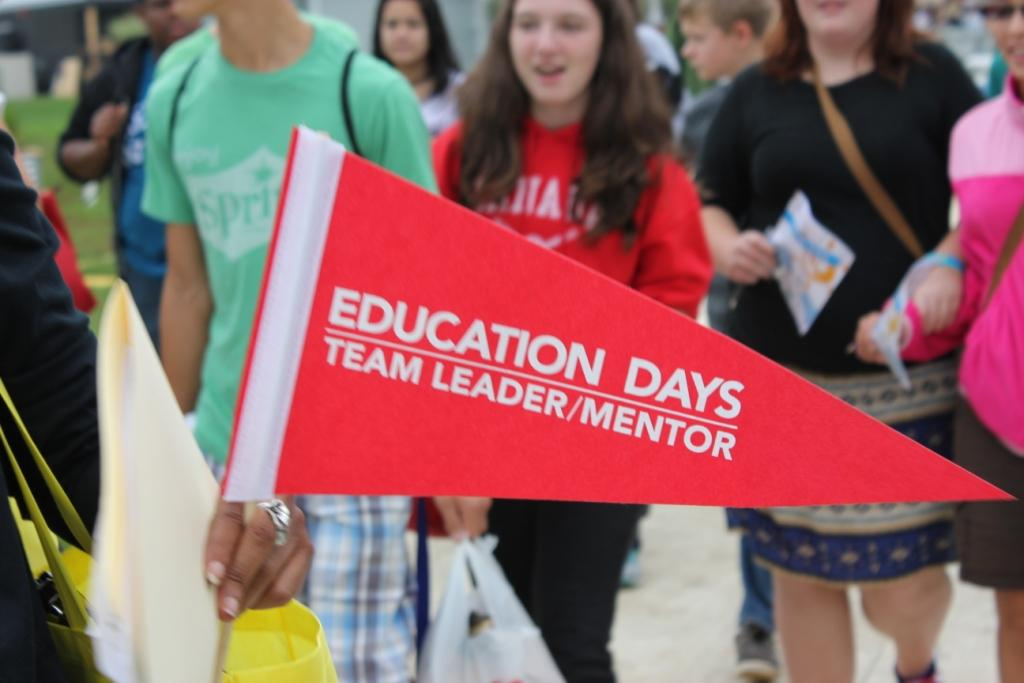 "Photo of a red flag that says ""Education Days Team Leader/Mentor."" In the background is a group of students."