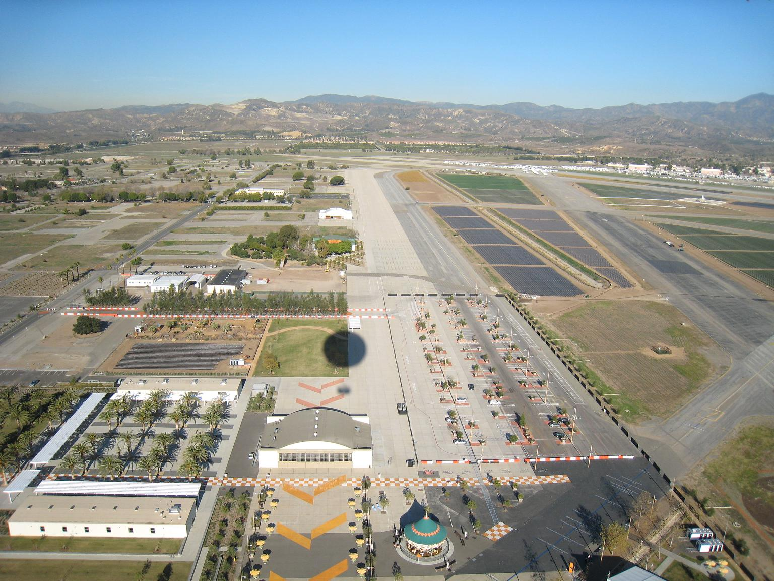 Photo of an air strip with mountains in the background.