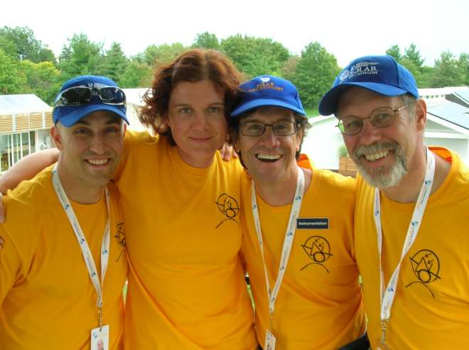 Photo of three men and one woman wearing gold shirts and Solar Decathlon hats.