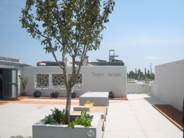 Photo of the inner courtyard of Team Israel's house, which includes benches and potted trees.