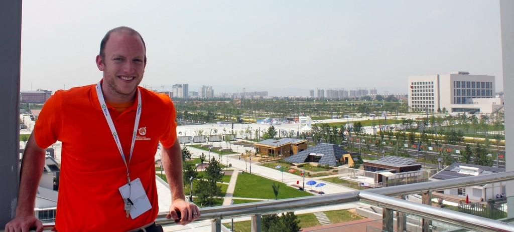 Photo of Joe Simon on balcony. The Solar Decathlon site is visible in the background.