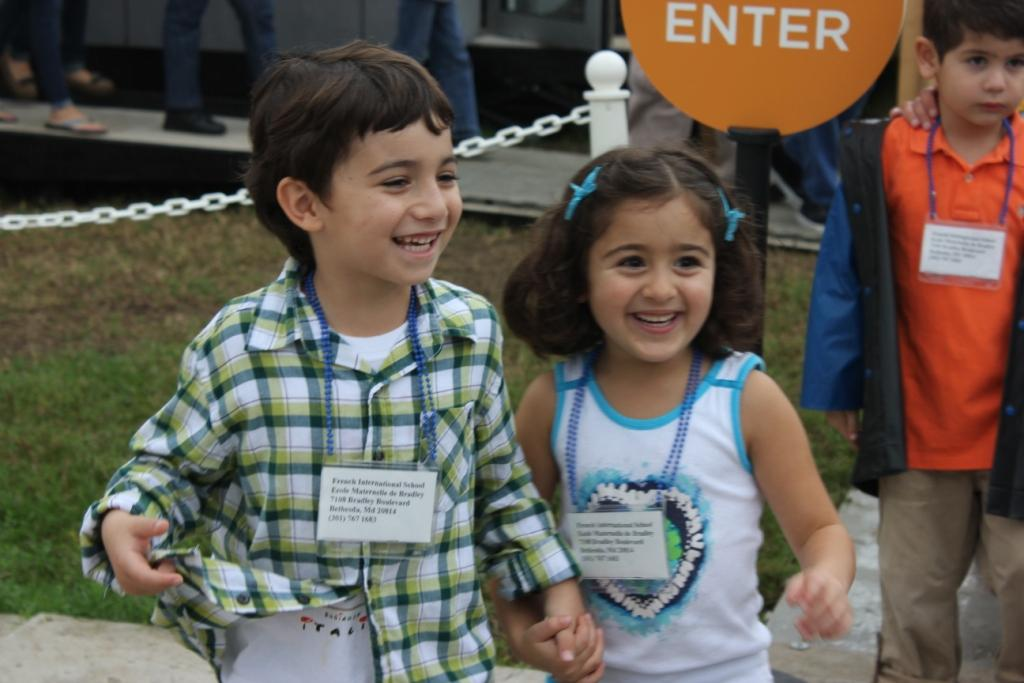 Photo of two children smiling and holding hands after leaving a competition house.