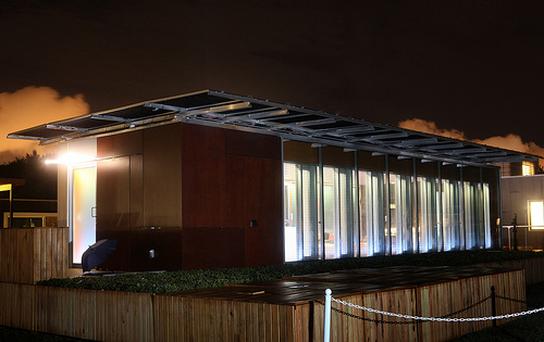Photo of a solar-powered house lit up at night.