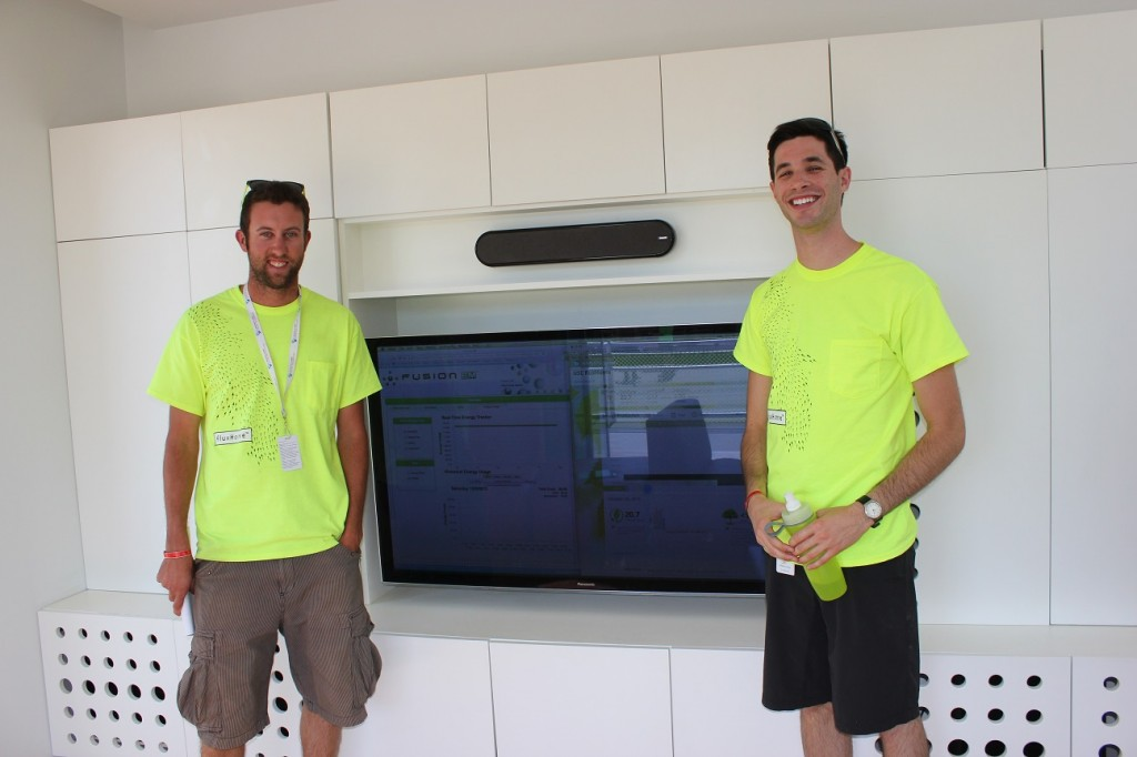 Photo of two decathletes standing on either side of a television.