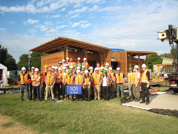 "Photo of a group of people wearing hard hats, safety vests, and safety glasses standing in front of a house. A sign in front reads ""101: New Zealand."""